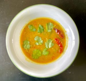 Sambar is a curry which is made from a tamarind-based broth, lentils, and vegetables.