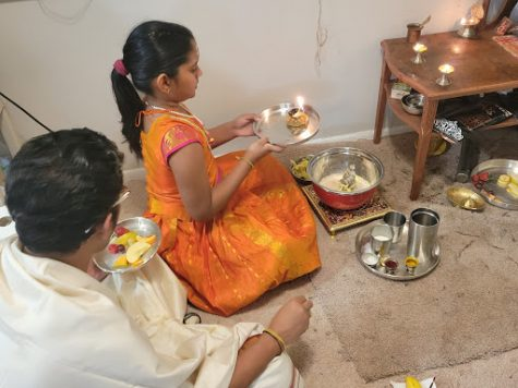 A fourth grade Ann Arbor student is doing arthi for the gods. The purpose of performing arti is the waving of lighted wicks before the deities in a spirit of humility and gratitude, wherein faithful followers become immersed in god